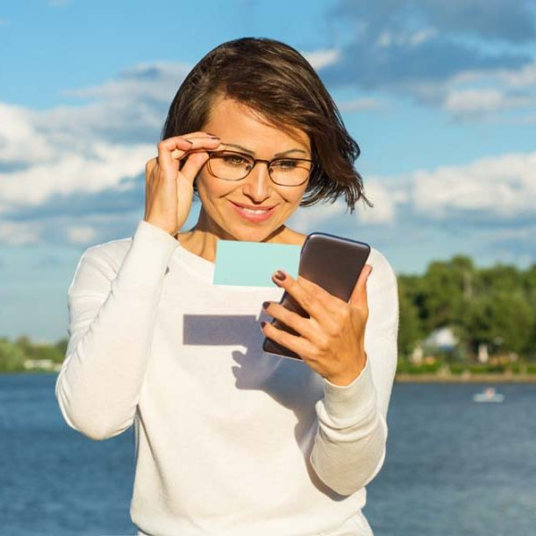 Business woman using app on a smart phone. On the background of the river holds a card and telephone